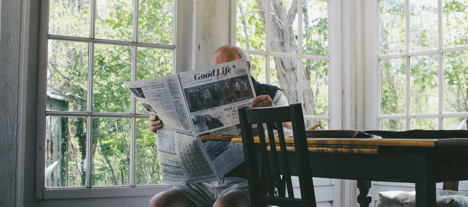 elderly parent reading the newspaper after moving in with child