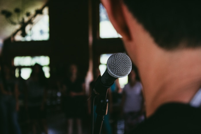 A photo of a performer takes the microphone and shares real estate negotiation tips