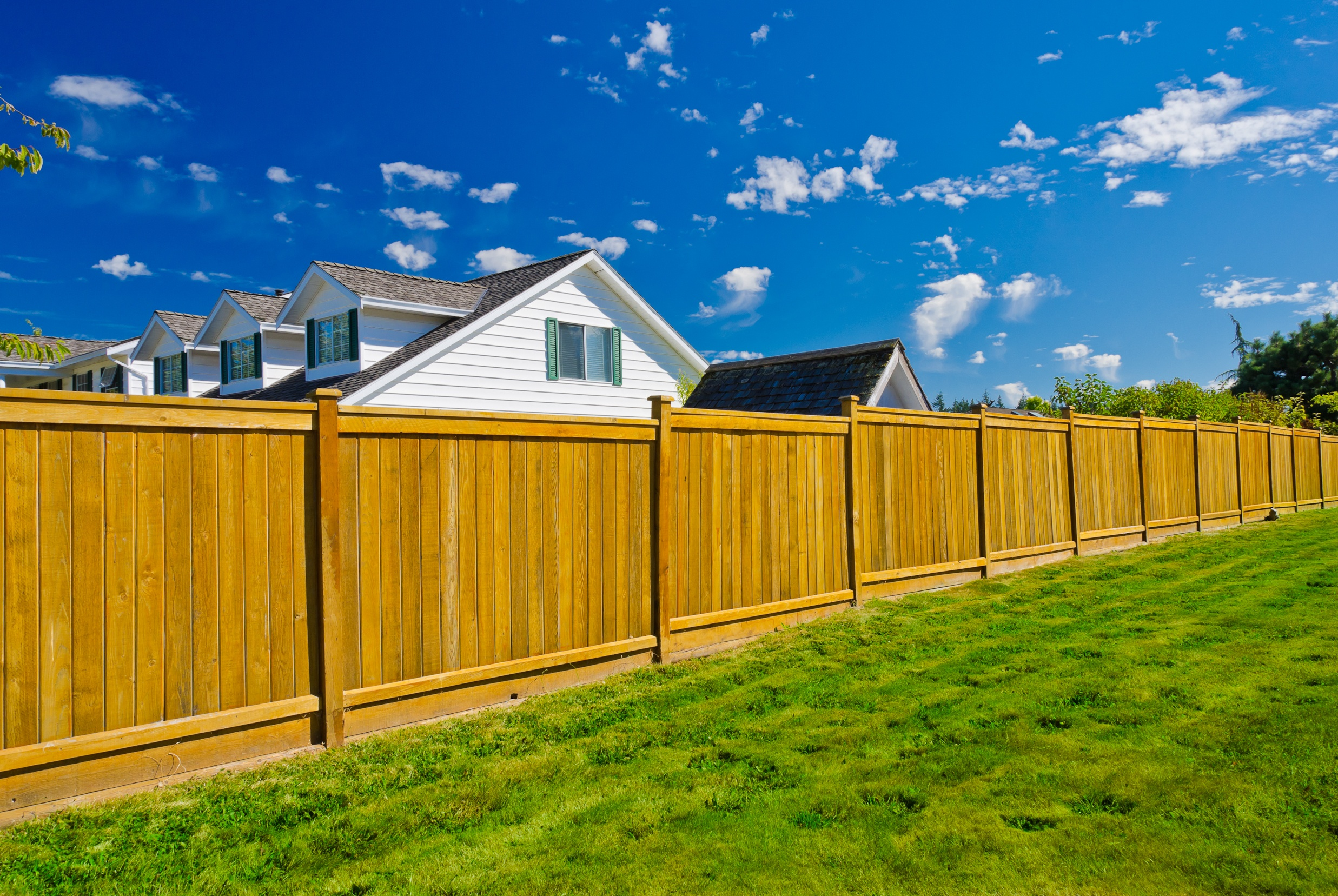 A new fence in a house's yard with value.