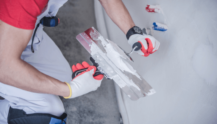 A person patching drywall to improve home maintenance.