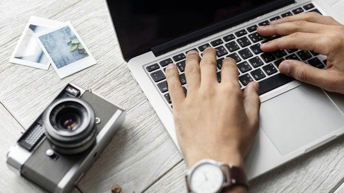 Un photographe immobilier faisant des recherches sur l'ordinateur.