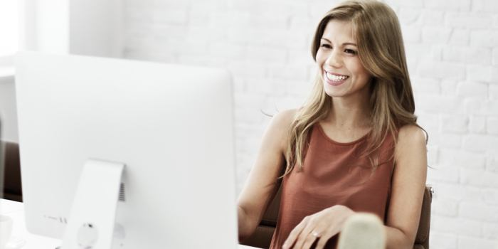 A female real estate agent helping find home comps on a computer.