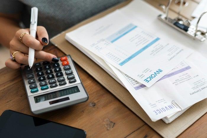 Woman calculating debts at closing meeting.