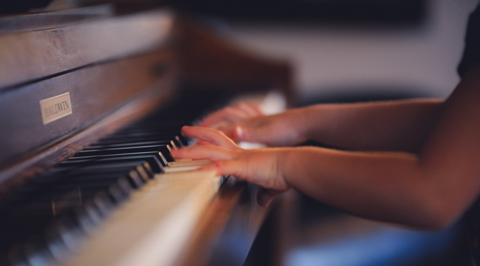 A person in retirement playing piano after cutting costs in housing.