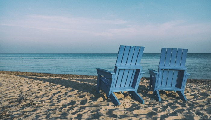 Two blue chairs on the beach for a couple after selling their house.
