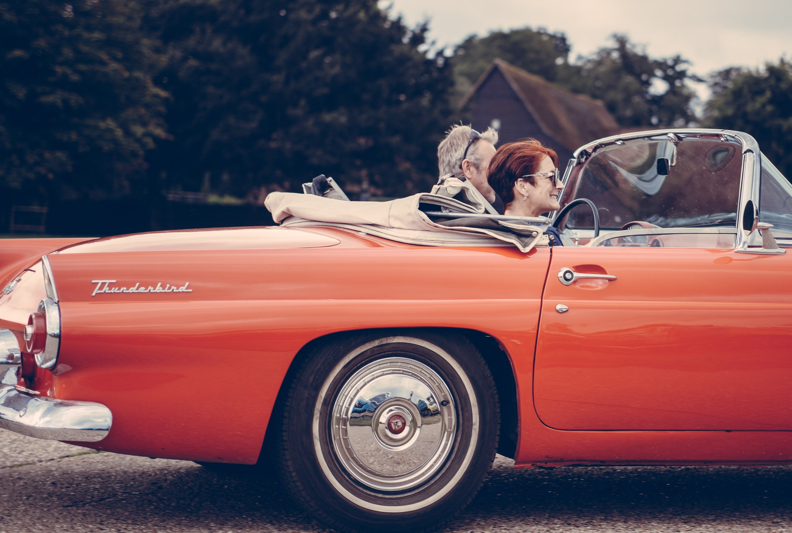 A couple in a red convertible using home equity for retirement.