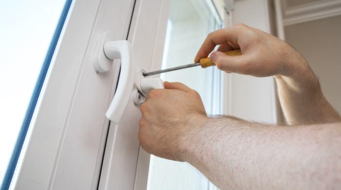 Window repair contractor fixing lock on window.