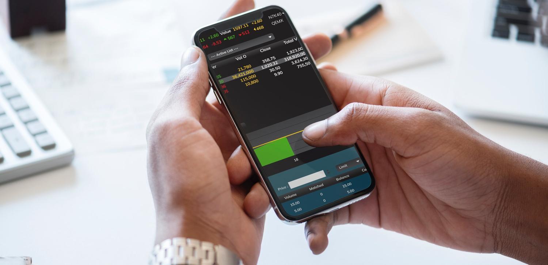 Man checks stock market crash on phone for housing market impact.