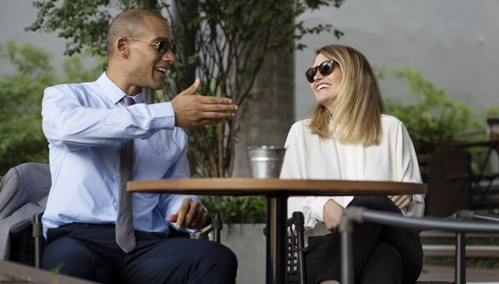 A man speaking to a woman about home appraisal referrals at an outside cafe.