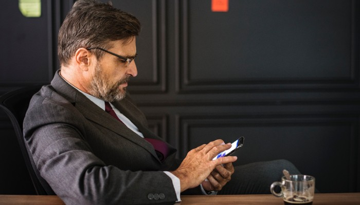 Realtor communicating with buyer and seller on smartphone
