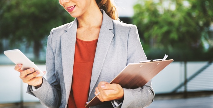 Female real estate agent holding clipboard and looking at phone.