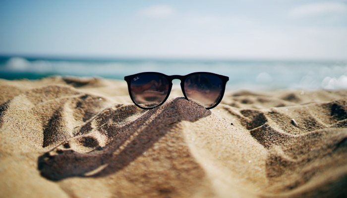 A pair of sunglasses on the beach in front of the ocean.