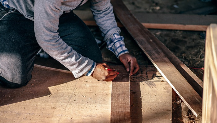 Man kneeling on the ground measuring plywood to cut.