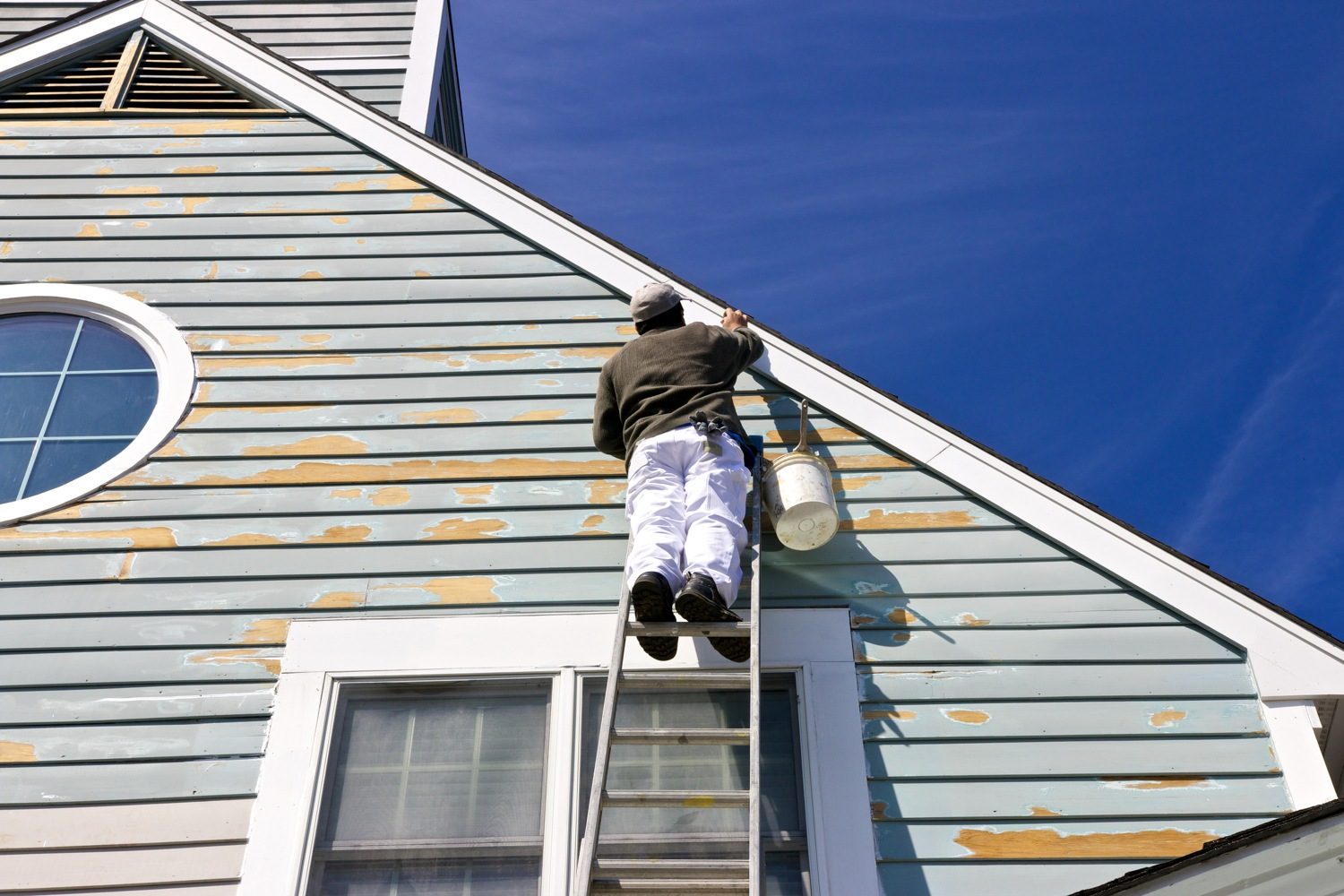 Man on ladder painting exterior of house with chipped paint.