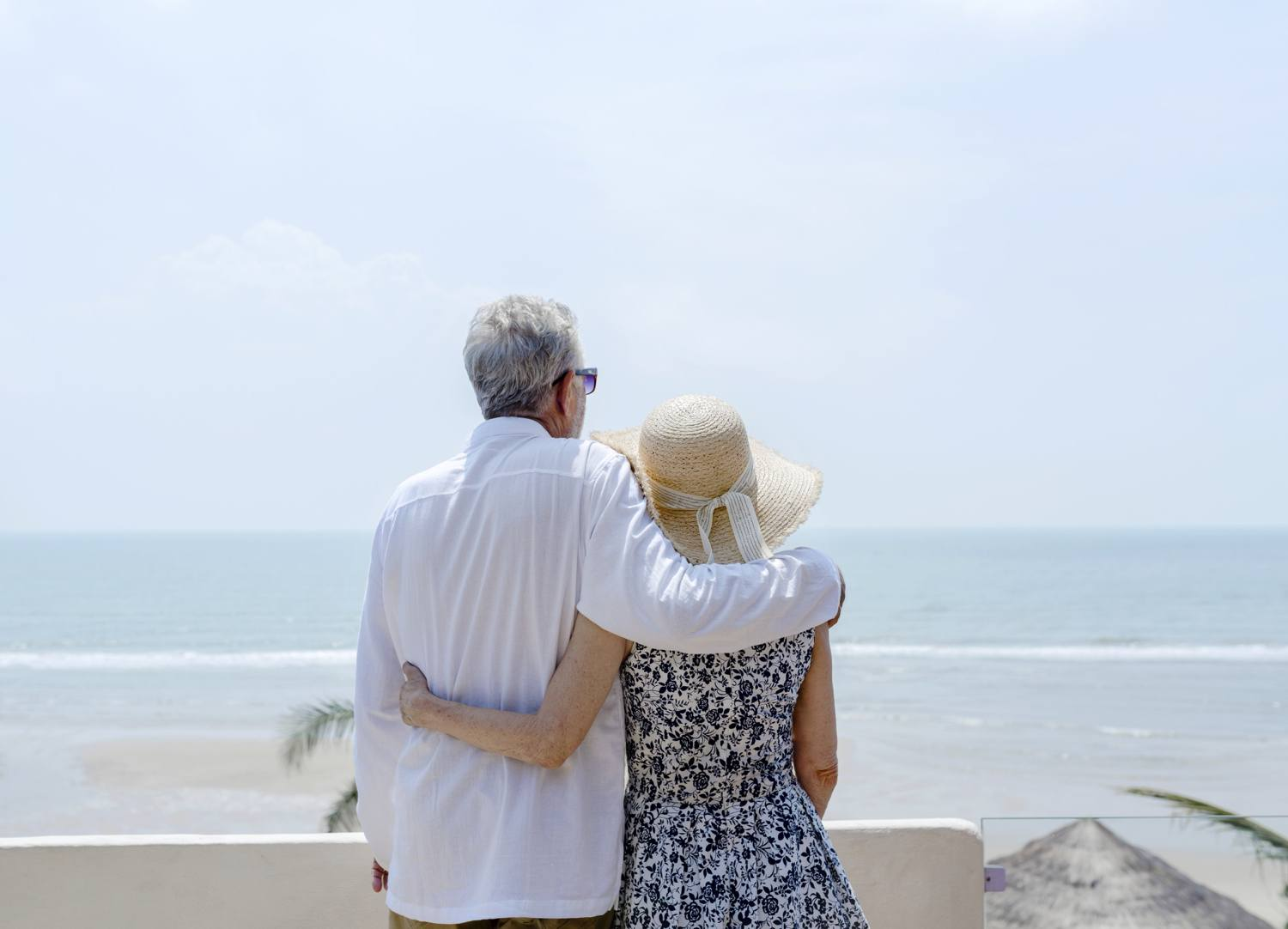 Retired couple looking out at ocean after downsizing.