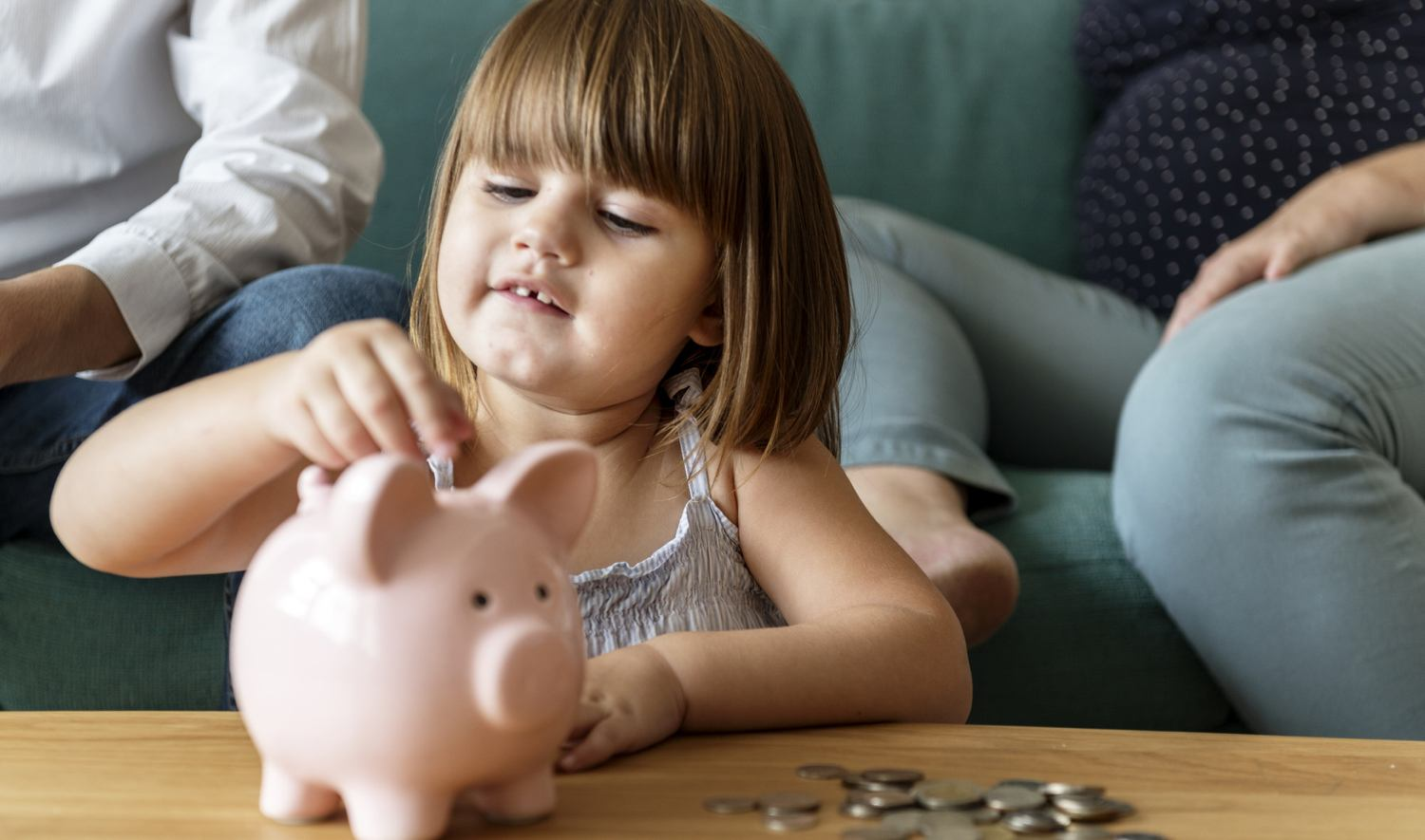 Child putting change in piggy back after downsizing home with family