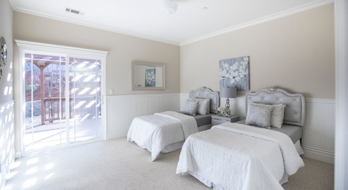 Bright bedroom with two twin beds during open house.