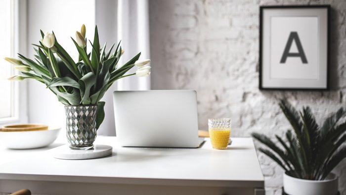 Open laptop and glass of orange juice at small kitchen table in downsized home.