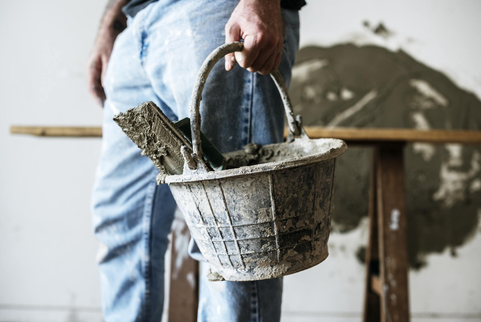 Home foundation repair professional holding bucket of tools.