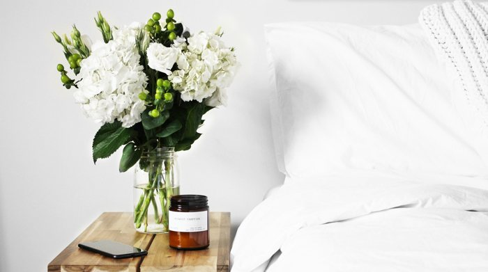 A small nightstand with flowers next to a white bed in a downsized home.
