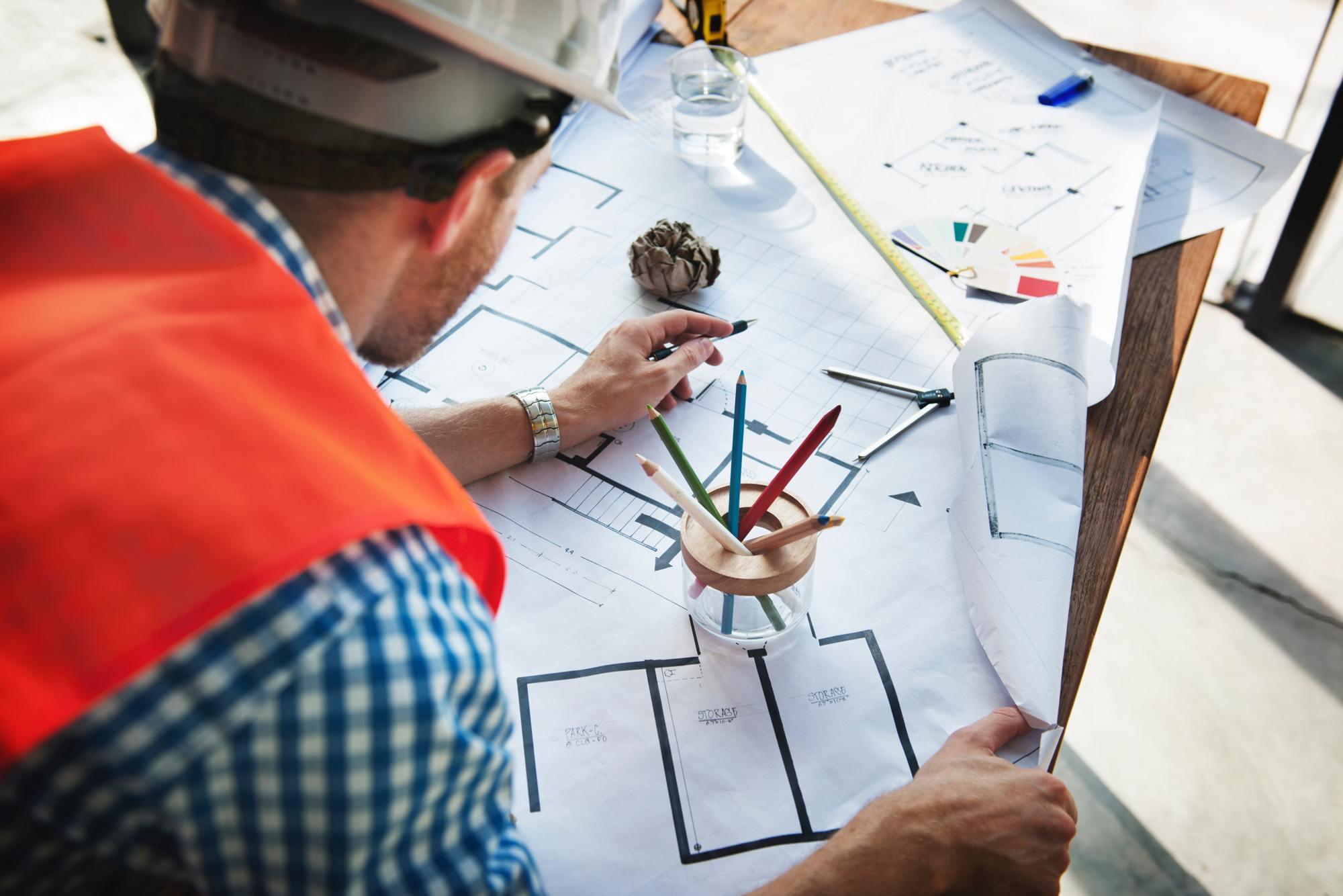 Home appraiser reviewing blueprints after appraisal.