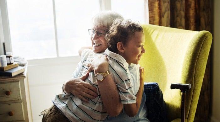 Retired grandmother hugging her grandson after downsizing her home.