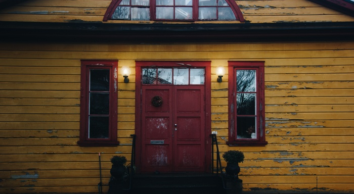 A House with yellow exterior paint, red doors and trim that has peeling paint.