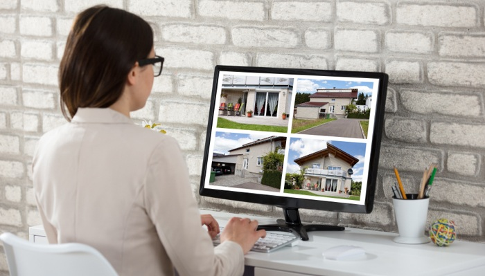 Female real estate agent editing photos on computer for real estate mailers.
