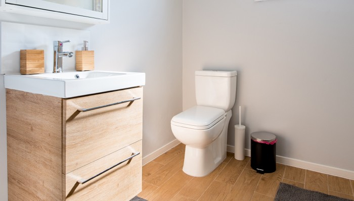 Toilet in home's bathroom with wood floors and finishes.