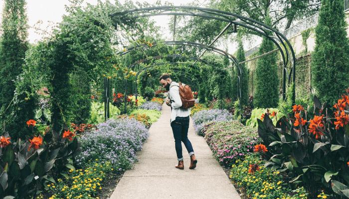 A man in a flower garden near a house for sale in Nashville.