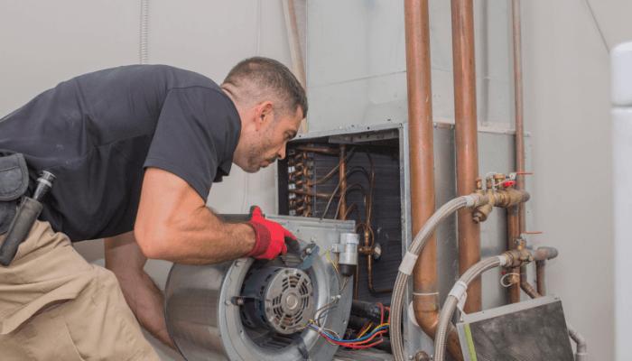 An maintenance professional repairing an HVAC unit in a home.
