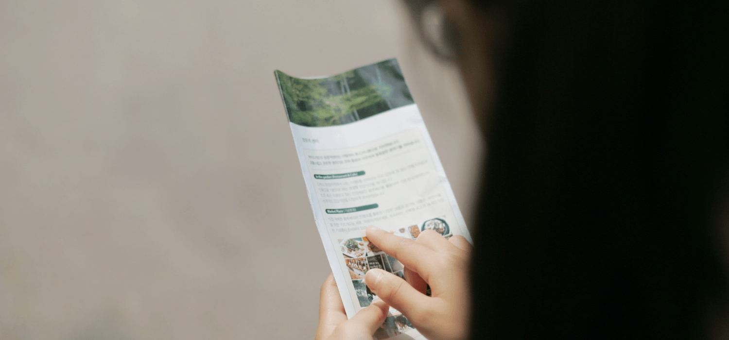 A woman reading an open house brochure.