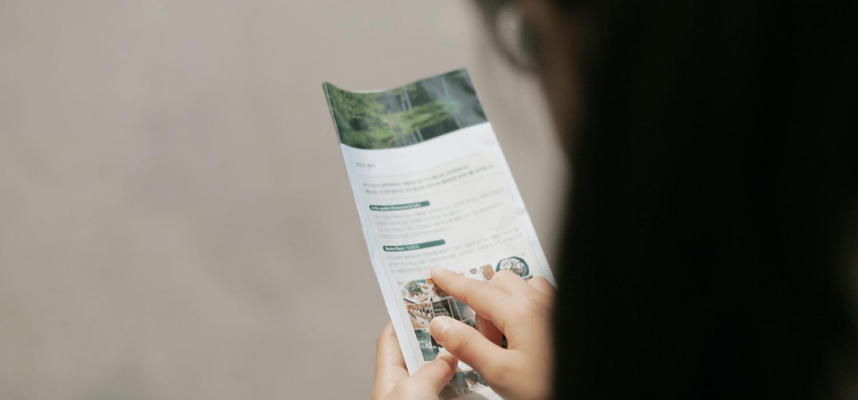 A woman reading an open house brochure.