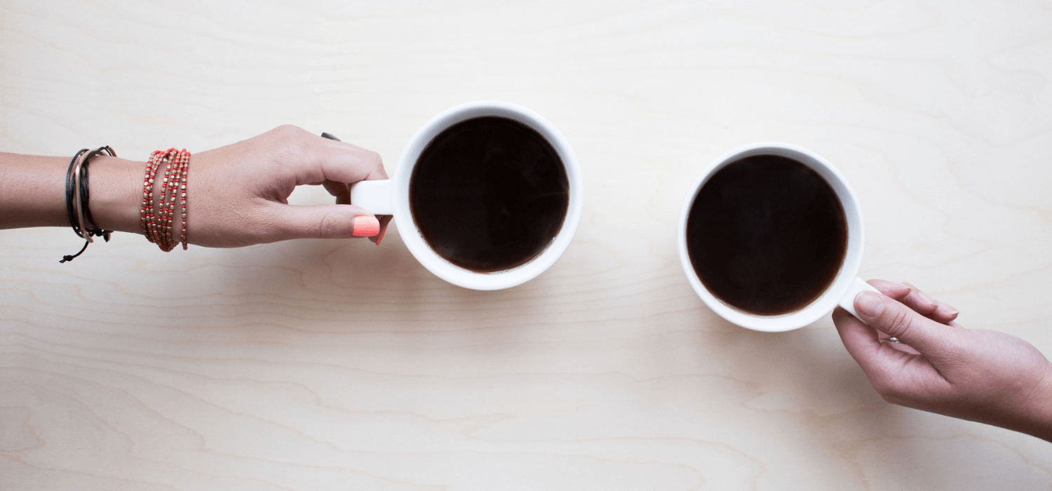 Two people negotiating over a house with two cups of coffee.
