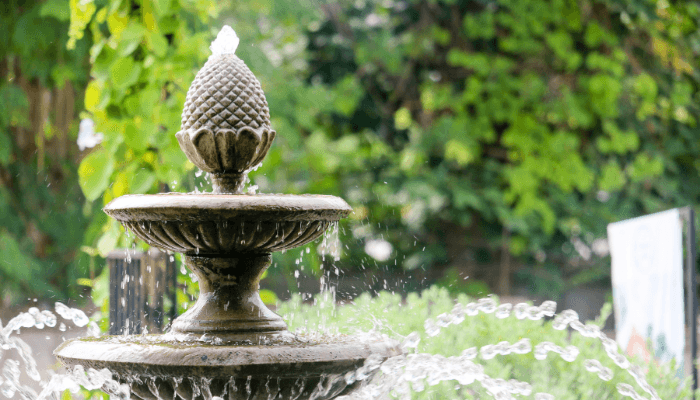 A fountain outside a house with road noise.