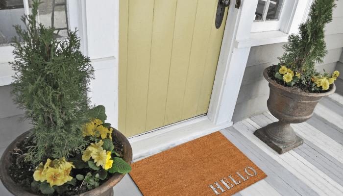 A door mat in front of a decorated entrance door.