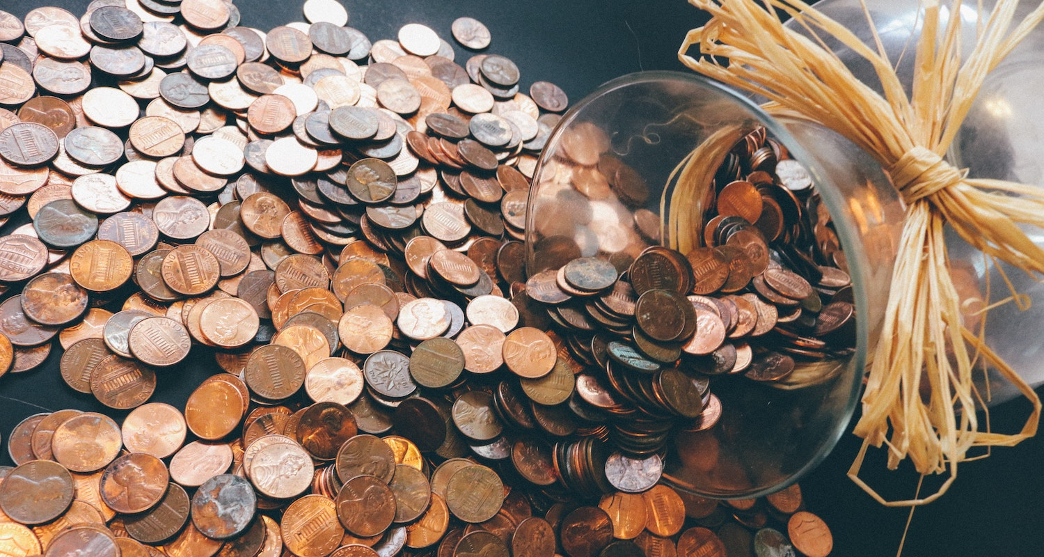 A jar of pennies spilling over a dark floor to represent first-time homebuyer loans