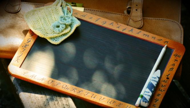 A handheld blackboard that a teacher would use.