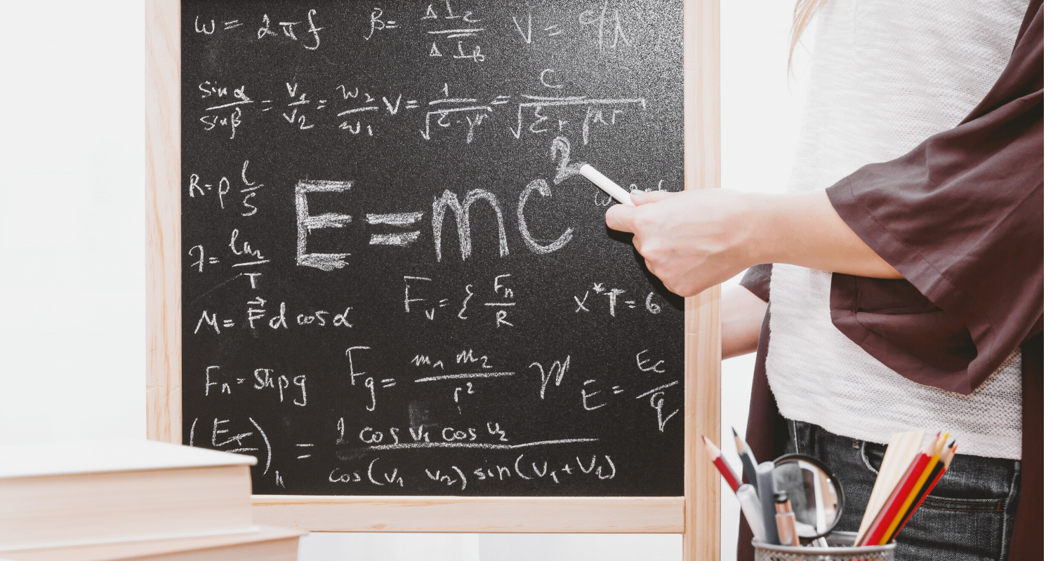 Equations on a blackboard with a teacher standing by.