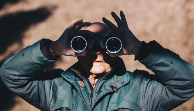 A man using binoculars.