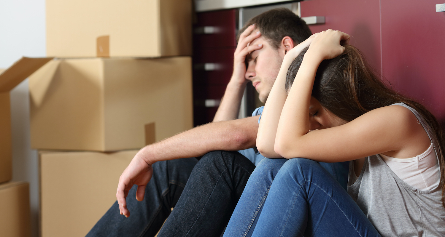 A stressed-out couple surrounded by moving boxes who are buying a house during coronavirus
