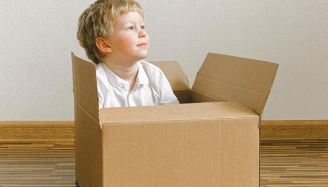 A little blond boy sitting in a cardboard moving box.