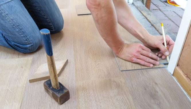 Hands measuring wooden floor tiles near a door with a sledgehammer nearby.