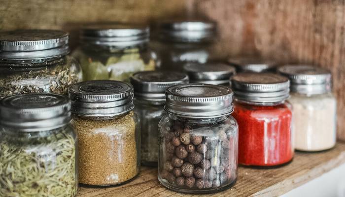 Varying sizes and kinds of spices in small glass jars on a wooden shelf.