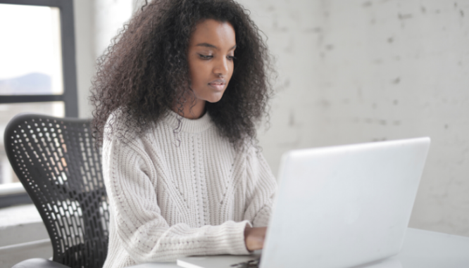 A black woman with shoulder-length hair working on a laptop in a room by herself.