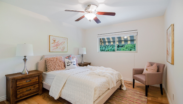 A white-themed bedroom with a ceiling fan and a window, in order to save money when moving into a new house.