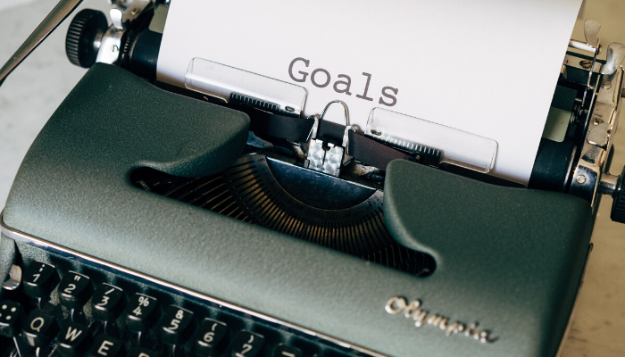 "A green typewriter with paper reading ""Goals"" loaded into it."