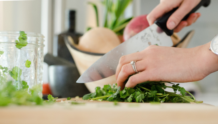A hand with a diamond wedding ring chipping herbs on a cutting board.