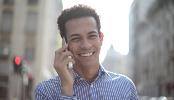 A man with brown hair and a blue striped shirt smiling while talking on the phone.