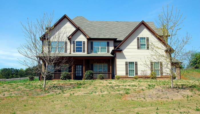 A beige two-story house with red shutters and a large yard that you could be selling.